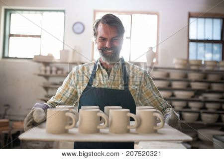 Happy male potter holding ceramic cups in tray at pottery workshop