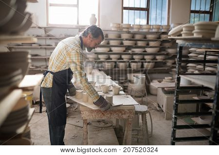 Male potter working at worktop in pottery workshop