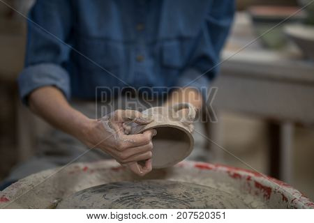 Mid section of female potter molding a cup in pottery workshop