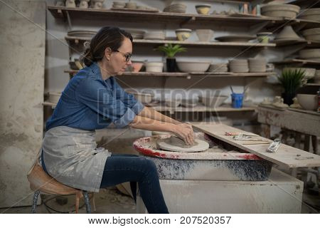 Female potter molding clay in pottery workshop