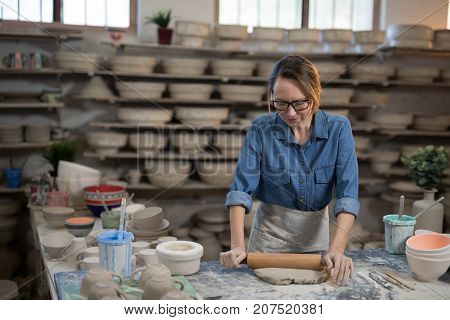 Female potter flattening the clay with rolling pin in workshop