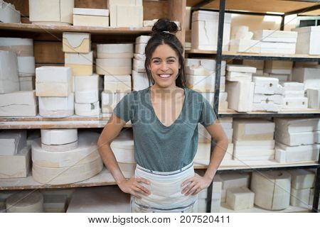 Portrait of female potter standing with hands on hip in pottery workshop