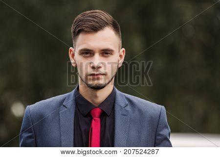 Portrait of successful confident businessman in dark business suit with red tie. Stylish confident man. Confident model. Be confident in business