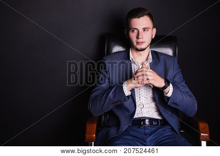 A successful young director in a business suit and white shirt  on a black leather chair. Stylish man in chair. Director of the firm. Director of a large firm. Confident director in chair