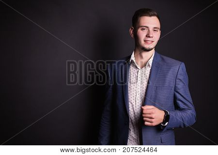 Successful young businessman in business suit and white shirt and fashionable clock on hand on a black background. Stylish businessman. Businessman professions. Confident businessman on a black background. Businessman in a business suit