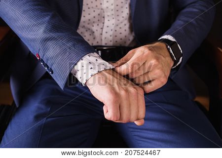 Successful young businessman in a business suit adjusts the sleeve on shirt and a fashionable clock on his arm. Successful man. Be successful in business. Successful director in the armchair. Successful worker