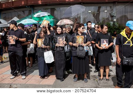 BANGKOK THAILAND - OCTOBER52017 : thai mourners people wearing black clothes and carrying photograph of king bhumibol on last day of respect to their beloved king at grand palace