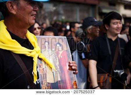 BANGKOK THAILAND - OCTOBER52017 : thai mourners people wearing black clothes and carrying king Bhumibol Adulyadej photograph on last day of respect to their beloved king at grand palace
