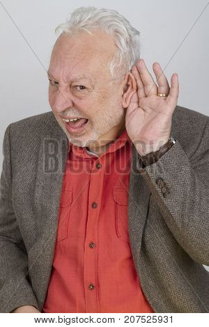 Bad hearing senior holding hand on his ear - on bright background