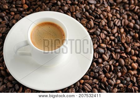 coffee cup espresso on background from cofee beans and plate.