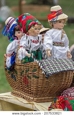 Dolls dressed in traditional Romanian folk costumes and exposed for sale at one traditional fair.
