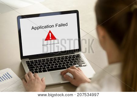 Girl looking at laptop with Application Failed error on screen. App stopped working, software failure, computer unit broke, system crashed unexpectedly, malware concept. Close up, focus on screen.