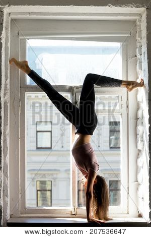 Young attractive woman practicing yoga, standing in Adho Mukha Vrksasana exercise, Downward facing Tree Pose pose, working out, wearing sportswear, black pants and top, indoor full length, window sill