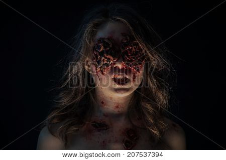 Portrait of a girl with realistic ulcers and worms crawling out of her eyes. creative halloween makeup.