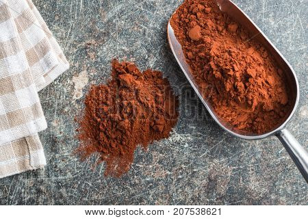 Tasty cocoa powder in scoop on old kitchen table. Brown cocoa.