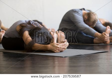 Group of young sporty people practicing yoga lesson with instructor in gym, sitting in paschimottanasana exercise, Seated forward bend pose, friends working out in club, indoor full length, studio