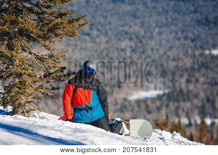 snowboarder with a snowboard in the snow against the background of the mountains.