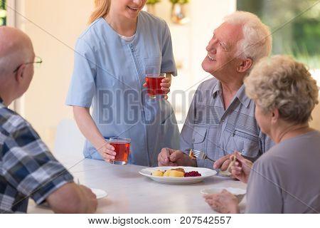 Nurse Giving Juice To Seniors