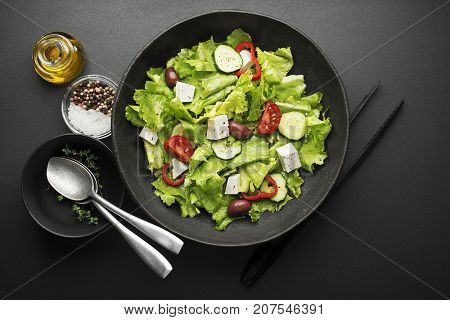 Green salad with cheese and fresh vegetables on a black background. Greek salad.