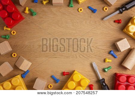 Kids toys frame background. Colorful toy tools, construction blocks and cubes on wooden table. Top view. Flat lay. Toned picture