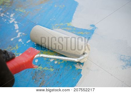 Close Up Of Paint Roller Painting A Metal Surface