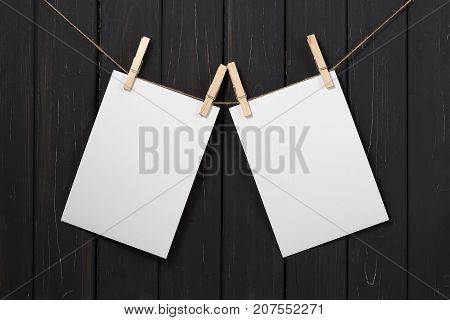 Two blank white paper cards hanging attach to rope with clothes pins on black wooden background