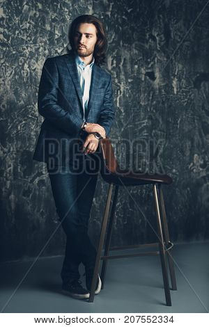 Vogue shot of a handsome man posing with an armchair at studio. Furniture and interior. Male beauty, fashion.