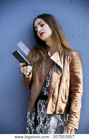 Trendy and attractive hipster woman is watching her mobile's screen in front of a blue wall background. City lifestyle concept.