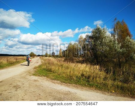 Old village man with backpack walking on the country road in autumn. Russian autumn landscape. Sand road. Bad russian roads. Forward to the horizon