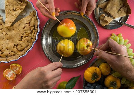 Caramel apples, American apple pie, hands over the table horizontal