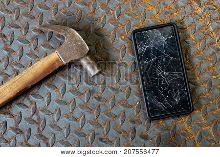 Broken mobile screen and hammer on old metal diamond plate or old checkered steel plate with rusty.