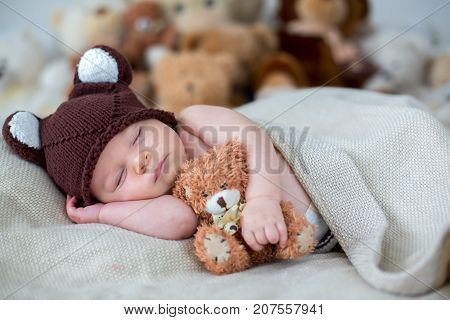 Little Newborn Baby Boy, Sleeping With Teddy Bear At Home In Bed