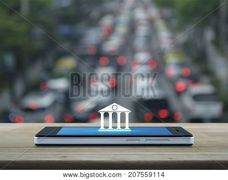 Bank icon on modern smart phone screen on wooden table over blur of rush hour with cars and road Mobile banking concept