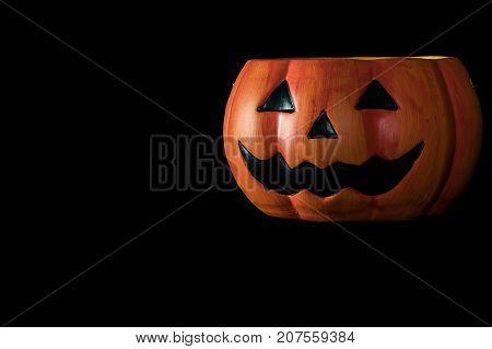 Halloween concept : Low key image of ceramic Halloween Pumpkin bucket isolated on black background