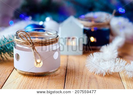 Christmas candles with Christmas tree decorations and a white candlestick house, white and blue and Christmas tree branches with a Christmas garland on a wooden table