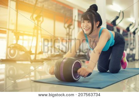 Using Abdominal Roller For Working Out Abdominals.