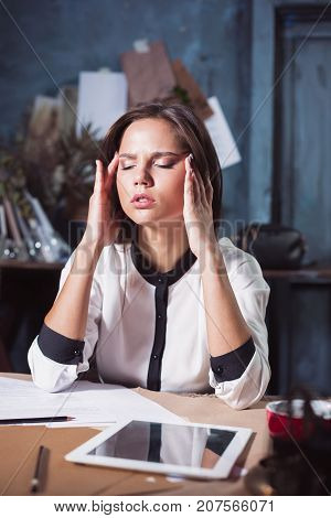 Young frustrated woman working at loft home or office desk in front of laptop suffering from chronic daily headaches