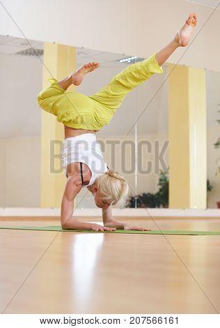 Beautiful sporty fit yogi woman practices yoga asana Vrischikasana Scorpion pose in the yoga class