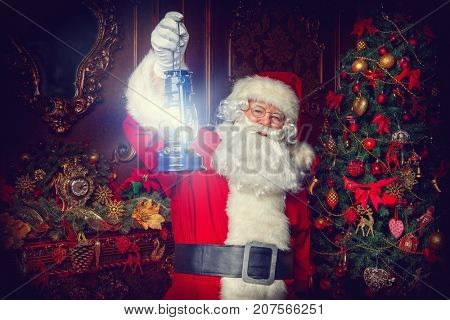 Christmas concept. Portrait of a fairytale Santa Claus standing with lantern in a beautiful Christmas room. Time of miracles.