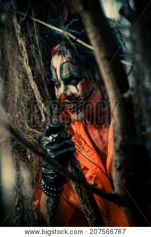 Close-up of a bloodthirsty clown man in a night forest. Halloween. Horror.