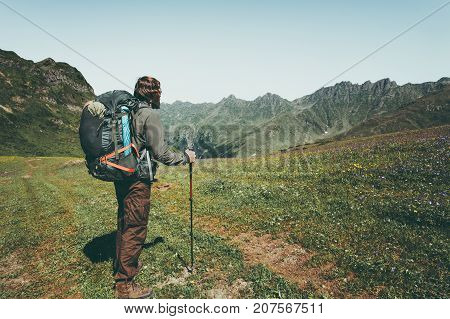 Man traveler hiking at mountains landscape Travel Lifestyle wanderlust adventure concept summer vacations outdoor into the wild with heavy backpack