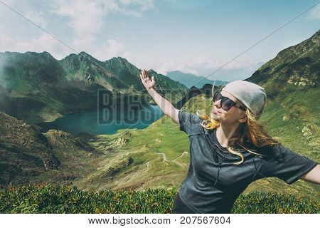 Woman wander lake in mountains raised hands Travel Lifestyle adventure concept happy emotions summer vacations outdoor exploring wild nature