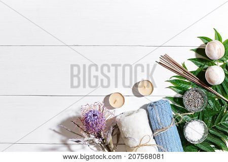 Spa set with sea salt, essential oil, soap and towel decorated with dry flower on white wooden background. Top view. Copy space. Still life. Mock-up. Flat lay