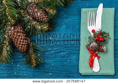 Christmas table place setting - blue table with green napkin, white fork and knife, decorated sprig of mistletoe and christmas pine branches. Christmas holidays background.