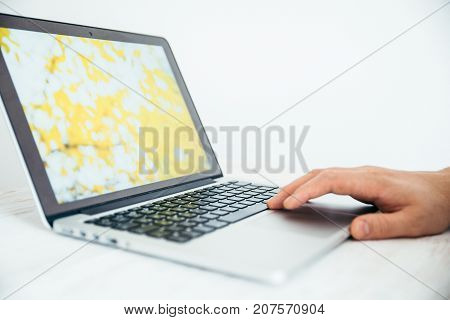 hand using touchpad on laptop white background