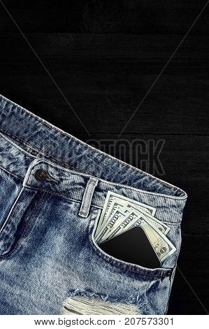 Cash and smart in your jeans pocket. Still life. Copy space. Top view on black background