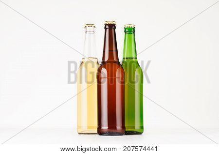 Group of brown green transparent longneck beer bottles 500ml mock up. Template for advertising design branding identity on white wood table.