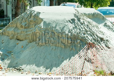 Big pile of sand on the urban city street reconstruction work site with part of orange plastic safety net around