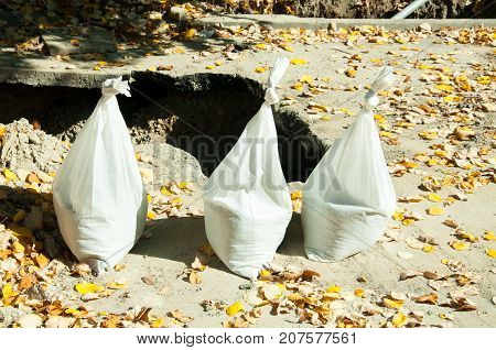 Three white plastic bags full of sand in front of the trench on the street reconstruction site and with orange autumn leaves around on the asphalt
