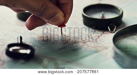 Closeup of hand pinning on world map journey travel